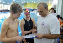 Mannschaftsleiter steht mit zwei Schwimmern am Beckenrand in der Schwimmhalle des Sportforums Chemnitz
